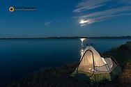 Campsite along Fort Peck Reservoir as full moon rises near Fort Peck, Montana, USA