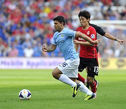 Manchester City's Sergio Aguero drives the ball past Cardiff City's Kim Bo-Kyung  - Photo mandatory by-line: Joe Meredith/JMP - Tel: Mobile: 07966 386802 25/08/2013 - SPORT - FOOTBALL - Cardiff City Stadium - Cardiff -  Cardiff City V Manchester City - Barclays Premier League