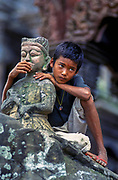 A young Nepali boy clings to a statue adorning the entrance to a temple in Patan, Kathmandu Valley