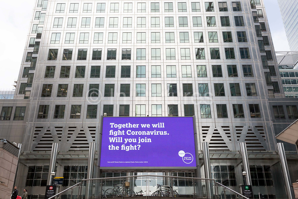 As the UKs Conornavirus pandemic lockdown continues, but with travel restrictions and social distancing rules starting to ease after three months of closures and isolation, a digital billboard from Guys and St. Thomas NHS hospitals advertises the fight against the Covid threat, at Canary Wharf, on 9th June 2020, in London, England.