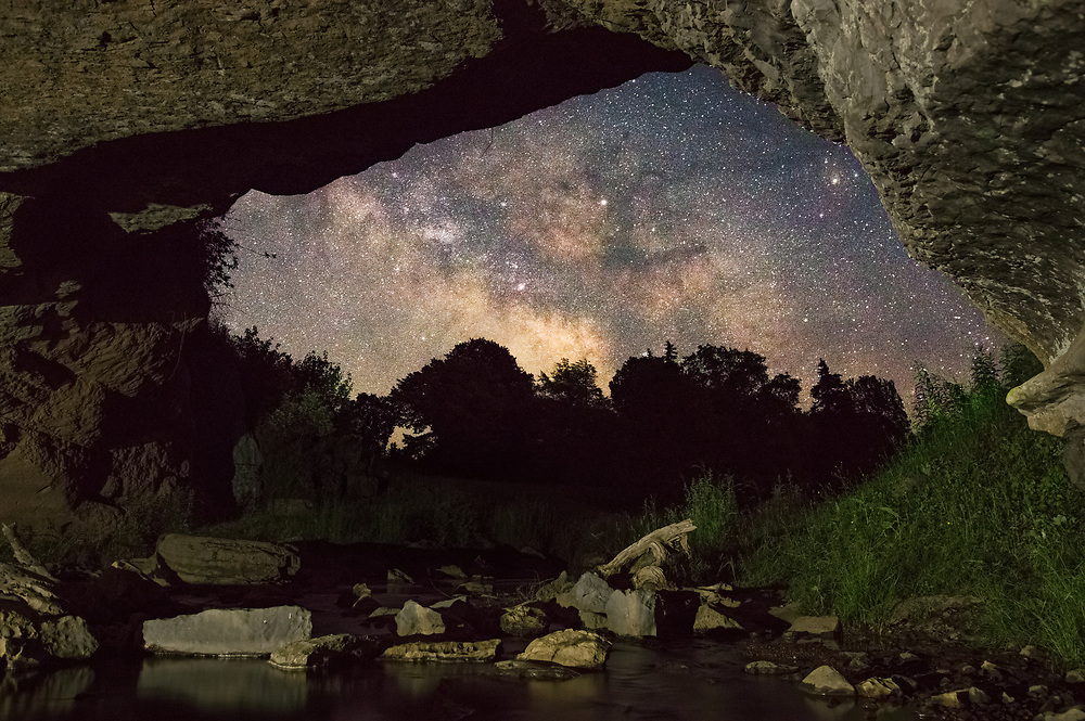 The Milky Way sits nestled in the natural stone frame of the Sinks of Gandy carved out over millenia by the creek that runs through it in the dark West Virginia countryside.