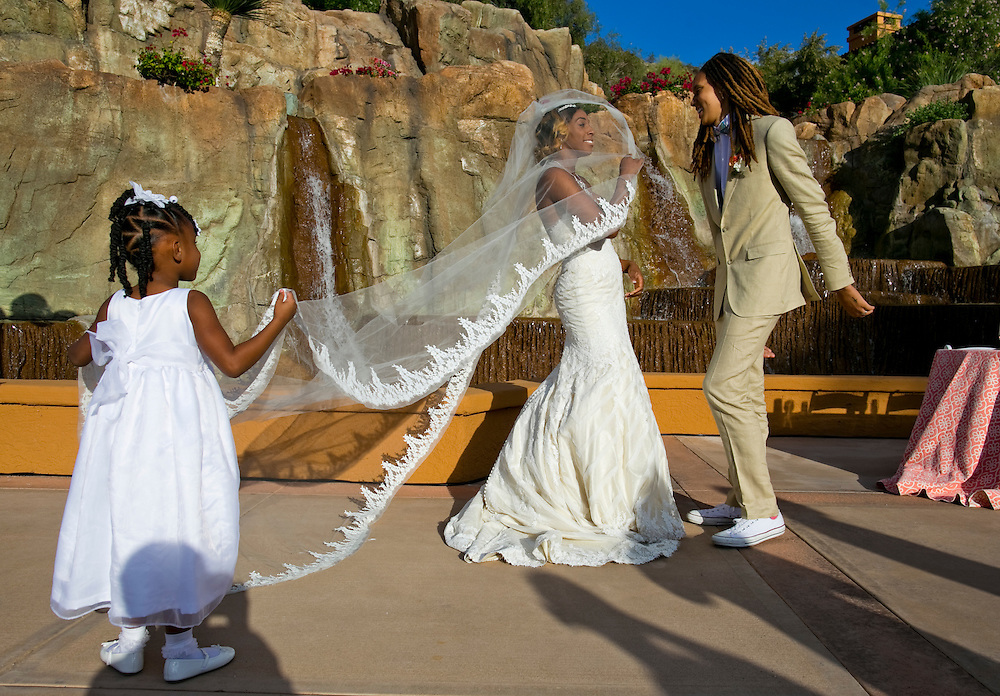 Phoenix Mercury center Brittney Griner, right and Glory Johnson, a fellow WNBA star who plays for the Tulsa Shock, dance during their wedding reception as their niece Sydney Griner, 5, holds Johnson's dress off the ground in Phoenix, Ariz. on May 8, 2015.