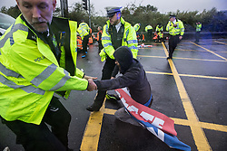 Colnbrook, UK. 27th September, 2021. Metropolitan Police officers remove Insulate Britain climate activists from a M25 slip road at Junction 14 close to Heathrow airport which they had blocked as part of a campaign intended to push the UK government to make significant legislative change to start lowering emissions. The activists are demanding that the government immediately promises both to fully fund and ensure the insulation of all social housing in Britain by 2025 and to produce within four months a legally binding national plan to fully fund and ensure the full low-energy and low-carbon whole-house retrofit, with no externalised costs, of all homes in Britain by 2030.