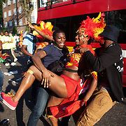 Two male spectators grap a female member of a dance troup and make her dance with them.  The Notting Hill Carnival has been running since 1966 and is every year attended by up to a million people. The carnival is a mix of amazing dance parades and street parties with a distinct Caribbean feel.