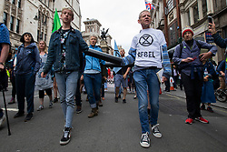 © Licensed to London News Pictures. 15/07/2019. London, UK. Extinction Rebellion protesters lock on and march outside The Royal Courts of Justice. They are campaigning against climate change.  Photo credit: George Cracknell Wright/LNP
