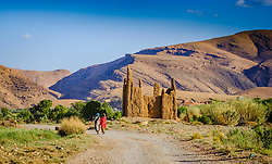 Two Berber women walk passed a ruined Kasbah in the M'Guin Gorge in southern Morocco<br /> <br /> (c) Andrew Wilson   Edinburgh Elite media