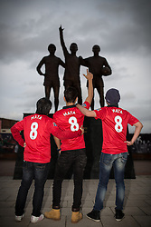 © Licensed to London News Pictures . 27/01/2014 . Manchester , UK . Thai tourists L-R Suthon Apinuntavach (50) , Putthipong W (35) and Soradetch Phetsangsailkul (35) pose with their new shirts , mirroring the United Trilogy statue . Their in Manchester to watch the Cardiff game tomorrow . Fans with new MATA 8 shirts in front of Old Trafford Football Ground as it's announced that Spaniard Juan Mata ( Juan Manuel Mata García ) has signed for Manchester United  . Photo credit : Joel Goodman/LNP