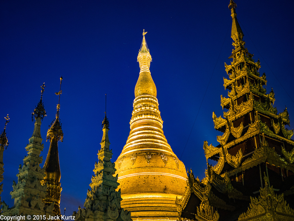 31 OCTOBER 2015 - YANGON, MYANMAR: Shwedagon Pagoda at night. Shwedagon Pagoda is officially known as Shwedagon Zedi Daw and is also called the Great Dagon Pagoda or the Golden Pagoda. It is a 99 metres (325ft) tall pagoda and stupa located in Yangon, Burma. The pagoda lies to the west of on Singuttara Hill, and dominates the skyline of the city. It is the most sacred Buddhist pagoda in Myanmar and contains relics of four past Buddhas: the staff of Kakusandha, the water filter of Koṇāgamana, a piece of the robe of Kassapa and eight strands of hair from Gautama, the historical Buddha. The pagoda was built between the 6th and 10th centuries by the Mon people, who used to dominate the area around what is now Yangon (Rangoon). The pagoda has been renovated numerous times through the centuries. Millions of Burmese and tens of thousands of tourists visit the pagoda every year, which is the most visited site in Yangon.      PHOTO BY JACK KURTZ