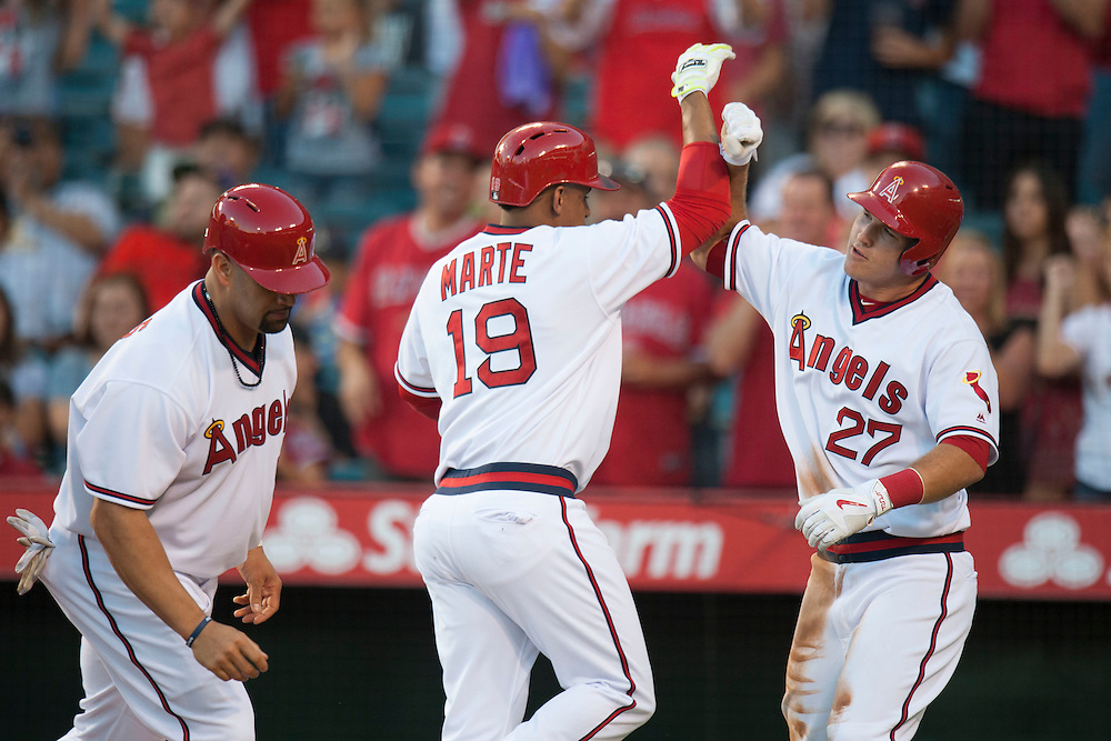 The Angels' Jefry Marte celebrates with Mike Trout and Albert Pujols after his three-run home run in the first inning against the Texas Rangers at Angel Stadium on Wednesday.<br /> <br /> ///ADDITIONAL INFO:   <br /> <br /> angels.0721.kjs  ---  Photo by KEVIN SULLIVAN / Orange County Register  -- 7/20/16<br /> <br /> The Los Angeles Angels take on the Texas Rangers at Angel Stadium.