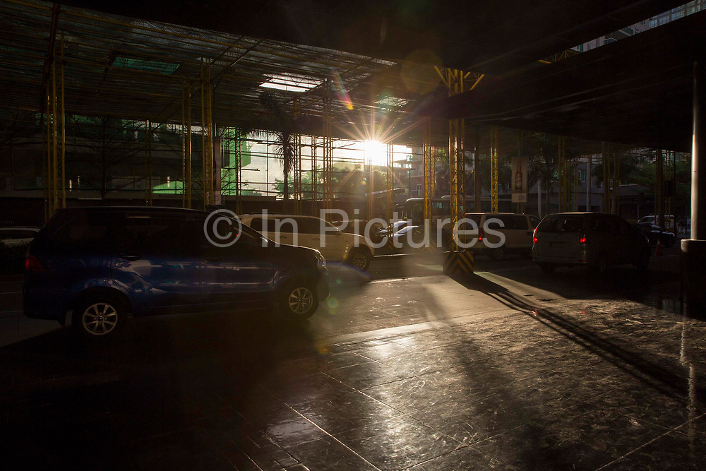 Cars driving under a scaffolding structure on Palm Drive, Makati in Manila, Philippines.