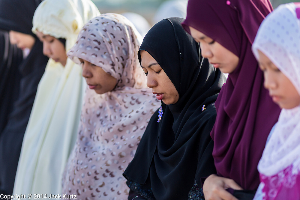 28 JULY 2014 - KHLONG HAE, SONGKHLA, THAILAND:  Women pray during Eid services at Songkhla Central Mosque in Songkhla province of Thailand. Eid al-Fitr is also called Feast of Breaking the Fast, the Sugar Feast, Bayram (Bajram), the Sweet Festival and the Lesser Eid, is an important Muslim holiday that marks the end of Ramadan, the Islamic holy month of fasting.  PHOTO BY JACK KURTZ
