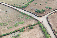 Aerial view of the countryside near Marrakech with a man on a motorbike driving on a small road.