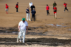 Embargoed to 0001 Monday August 28 A batsman leaves the ground after being hit out during a match between the Ship Inn Cricket Club and the Eccentric Flamingoes Cricket Club on Sunday April 30th, 2017, in front of the pub in Elie, Fife, which is the only one in Britain to have a cricket team with a pitch on the beach. The Ship Inn Cricket Club season runs from May to September with dates of matches dependent on the tides. Any Batsman who hits a six which lands in the Ship Inn beer garden wins their height in beer and any spectator who catches a six in the beer garden also wins their height in beer.