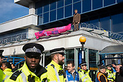 A climate change protester stands on a roof at London City Airport during day four of two weeks of planned demonstrations on 10th October, 2019 in London, Untited Kingdom. Extinction Rebellion is demanding that governments drastically cut carbon emissions.