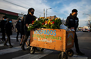 Jason Perez, 17, and Joshua Perez, 16, push the raspados cart of their grandfather, Guadalupe Perez Alarcon, 61, down 26th Street in a procession from his memorial service in Little Village on Wednesday, Nov. 18, 2020. Alarcon, a raspados vendor who would station his cart outside the La Chiquita store on 26th Street every summer for 20 years, died of COVID-19 on Sunday. (Brian Cassella/Chicago Tribune)