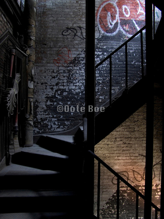 a dark and mysterious looking stairway with graffiti and fire hose