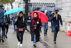 © Licensed to London News Pictures. 21/10/2019. London, UK. Tourists shelter from rain underneath umbrellas on a wet and cold day in Westminster, London. Photo credit: Dinendra Haria/LNP