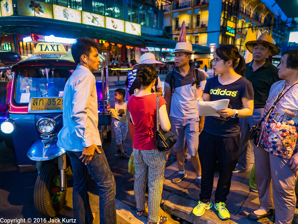 """28 JULY 2016 - BANGKOK, THAILAND:    Chinese tourists try to flag down a """"tuk-tuk"""" or three wheeled taxi on Ratchadamri Road. Bangkok city authorities have promised to evict the street vendors on Ratchadamri by August 1, 2016.       PHOTO BY JACK KURTZ"""