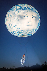 © Licensed to London News Pictures . 18/07/2013 . Suffolk , UK . A woman suspended from a moon balloon as Studio Festi perform Water Dance above a lake in Henham Park after sunset on the opening night of The Latitude music and culture festival in Henham Park , Southwold . Photo credit : Joel Goodman/LNP