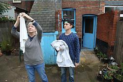 Teenager helping grandmother with hanging washing