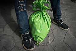 A Honduran migrant tied his shoes with string to stop the soles falling off. In southern Mexico he had to walk two weeks, day and night with little sleep in extreme temperatures, then he was chased by migration police through rough terrain for hours and his shoes fell apart. He also lost his backpack during a chase, he has fashioned a backpack from a plastic bag and some rope.