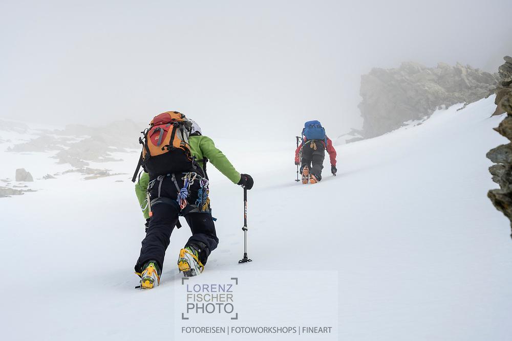 Zwei Skibergsteiger im Aufstieg durch das 900 Meter hohe Südwand-Couloir am Lauteraarhorn im Nebel, Berner Oberland, Schweiz<br /> <br /> Two ski mountaineers ascending through the 900-meter-high Südwand-Couloir at Lauteraarhorn in the fog, Bernese Oberland, Switzerland
