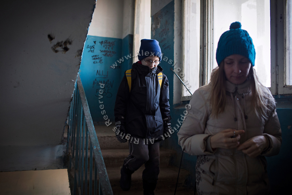 Yaroslav, 10, is going out with his mother Olga, 36, to use his UNICEF video camera, near the provisional home where they live as internally displaced persons. (IDPs) Yeroslav is taking part to the UNICEF-sponsored One Minute Junior project for internally displaced persons (IDPs), carried out by the local NGO 'Ukrainian Frontiers' in the city of Kharkiv, the country's second-largest, in the east. The conflict between Ukrainian army and Russia-backed separatists nearby, in the Donbass region, have left more than 10000 dead since April 2014, including over 1000 since the shaky Minsk II ceasefire came into effect in February 2015. The approximate number of people displaced by the conflict is 1.4 million as of August 2015. Yeroslav's mother, Olga, is also a participant to a different project of 'Ukrainian Frontiers', called 'Self-Employment', first as a beneficiary, and now as a paid hotline coordinator for people seeking jobs and formation courses.
