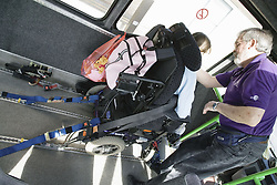 Man securing wheelchair of child with physical disability into ambulance,