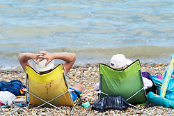 ©Licensed to London News Pictures 06/08/2020  <br /> Minster-on-sea, UK. A couple sunbathing on their sun loungers. Hot sunny weather today as people visit the beach at Minster-on-sea, Isle of sheppey in Kent. Photo credit: Grant Falvey/LNP
