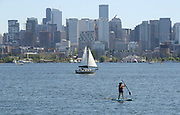 Boats of all sizes gather on Lake Union, including the sailboat and a paddle boarder. (Greg Gilbert / The Seattle Times)
