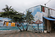 Painted wall outside a house representing an exotic scenery of seascape and coconut trees. Clothes dry outside. Vietnam, Asia