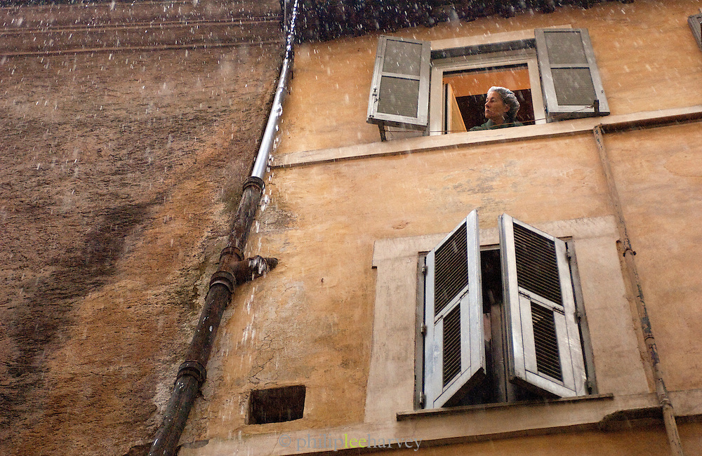 Woman looking from a window in the rain, Rome, Italy