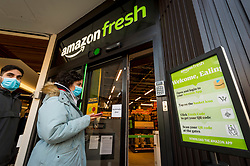 "© Licensed to London News Pictures. 07/03/2021. LONDON, UK.  Customers enter the new 2,500 sq ft Amazon Fresh store in Ealing, west London on its first weekend of opening. It is the first ""just walk out"" grocery store in the UK and the first outside the USA.  As a ""contactless"" shop, it is available to anyone signed up to Amazon and with the app on their smartphone.  In-store cameras and artificial intelligence monitor customers picking up items who simply walk out and billing takes place later automatically.  Photo credit: Stephen Chung/LNP"