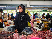 18 JUNE 2015 - PATTANI, PATTANI, THAILAND: A woman sells meat in the market in Pattani. Many Thai Muslims go shopping early in the day to buy food for Iftar, the meal that breaks the day long Ramadan fast.    PHOTO BY JACK KURTZ