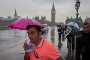 During a downpour, an afternoon of heavy rain in London, drenched and wet tourists and visitors cross Westminster Bridge including this man carrying a childs umbrella, England on 7th June 2016.