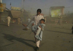 PARACHINAR, June 23, 2017 - Parachinar, Pakistan -  A man helps an injured child near a blast site in northwest Pakistan's Parachinar. At least 18 people were killed and over 100 others injured as twin blasts ripped through a market on Friday afternoon in Parachinar, capital city of Pakistan's northwest tribal area of Kurram Agency, reported local Urdu TV channel Geo.  <br />  (Credit Image: © Stringer/Xinhua via ZUMA Wire)