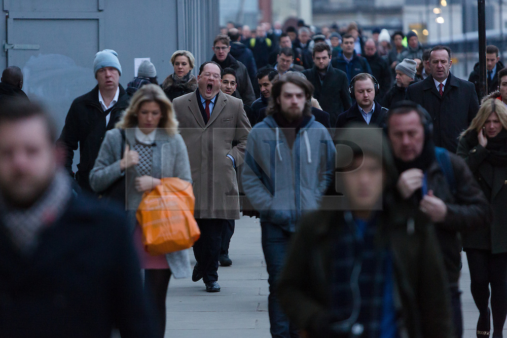 """© Licensed to London News Pictures. 18/01/2016. London, UK. Commuters crossing London Bridge this morning. Today, known as """"Blue Monday"""" is meant to be the most depressing day of the year. Photo credit : Vickie Flores/LNP"""