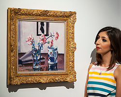 """© Licensed to London News Pictures. 18/11/2016. London, UK. A staff member views """"Pink Carnations"""" by Francis Campbell Boileau Cadell (est. GBP200-300k), at the preview at Sotheby's of works on view at four upcoming November auctions featuring Modern & Post-War British Art, A Painter's Paradise (Julian Trevelyan & Mary Fedden at Durham Wharf), Scottish Art and Picasso Ceramics from the Lord & Lady Attenborough Private Collection. Photo credit : Stephen Chung/LNP"""