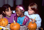 Multicultural friends age 8 painting pumpkins at Youth Express Halloween party.  St Paul  Minnesota USA