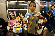 Roma Gypsy child playing accordion in underground metro to earn a living. Roma Gypsies victims of racism and discrimination, often forcibly evicted or moved from one camp to another, marginalized, living on the periphery of urban centres. The Roma Gypsies originated from India where they left over a thousand years before. Tribes moved across Euroasia eventually arriving in Europe in the 14th century. They have survived 500 years of slavery and persecution. They moved from place to place, often nomadic in search of work. Now many live in container camps, some are unemployed, others work the markets, or import export. Rome, Italy.