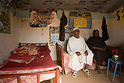 """Mr Matar Mohammed, a former farmer from Taweela, a Darfur village sits with his wife in the 4 sq km Abu Shouk refugee camp, (disputedly) home to 38,000 displaced persons, on the outskirts of Al Fashir. Mr Mohammed was once a successful farmer who grew tobacco and sorghum and has occupied this house with his 14 family members since May 2004, surviving on twice a day aid hand-outs. Many family members and friends have been killed . """" We had a good life,"""" he says adding """"we would go back if security was guaranteed .."""""""