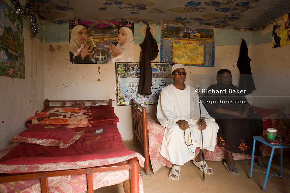 "Mr Matar Mohammed, a former farmer from Taweela, a Darfur village sits with his wife in the 4 sq km Abu Shouk refugee camp, (disputedly) home to 38,000 displaced persons, on the outskirts of Al Fashir. Mr Mohammed was once a successful farmer who grew tobacco and sorghum and has occupied this house with his 14 family members since May 2004, surviving on twice a day aid hand-outs. Many family members and friends have been killed . "" We had a good life,"" he says adding ""we would go back if security was guaranteed .."""