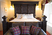 Oak bed in stylish bedroom with tartan furnishings at luxurious upmarket Ullinish Lodge Hotel at Struan, Isle of Skye, Western Isles of Scotland
