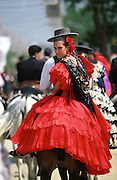 """Riders on horseback, men and women dress up in their finery, the traditional """"traje corto"""" (short jacket, tight trousers and boots) for men and the """"faralaes"""" or """"trajes de flamenca"""" (flamenco style dress) for women. The men traditionally wear hats called """"cordobés""""...The Feria de abril de Sevilla, """"Seville April Fair"""" dates back to 1847. During the 1920s, the feria reached its peak and became the spectacle that it is today. It is held in the Andalusian capital of Seville in Spain. The fair generally begins two weeks after the Semana Santa, Easter Holy Week. The fair officially begins at midnight on Monday, and runs six days, ending on the following Sunday. Each day the fiesta begins with the parade of carriages and riders, at midday, carrying Seville's citizens to the bullring, La Real Maestranza...For the duration of the fair, the fairgrounds and a vast area on the far bank of the Guadalquivir River are covered in rows of casetas (individual decorated marquee tents which are temporarily built on the fairground). Some of these casetas belong to the prominent families of Seville, some to groups of friends, clubs, trade associations or political parties. From around nine at night until six or seven the following morning, at first in the streets and later only within each caseta, crowds of people party and dance Sevillanas, traditional Flamenco dances, Sevillan style drinking Jerez sherry, or Manzanilla wine, and eating tapas."""