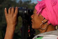 Lisu people, Woman looking through binoculars searching for wildlife in Xiang Bai village, Dehong, Yunnan, China