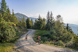 Two mountain biker friends riding on dirt road through forest, Zillertal, Tyrol, Austria