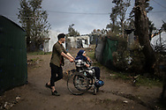 An elderly woman from Afghanistan is helped to reach the tent where she lives with her husband. About 20000 are living in a makeshift camp nearby the city of Moria on the island of Lesbos in miserable conditions, most of the without water, electricity nor sanitary facilities.  Federico Scoppa