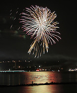 Beacon, New York -  Independence Day fireworks explode in the sky over Newburgh and reflected in the Hudson River as seen from a waterfront park on July 4, 2010. ©Tom Bushey / The Image Works