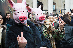 "London, April 16th 2016. Two ""pigs"" make obscene gestures in Trafalgar Square as thousands of people supported by trade unions and other rights organisations demonstrate against the policies of the Tory government, including austerity and perceived favouring of ""the rich"" over ""the poor""."