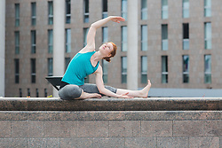 Young woman doing yoga on wall in urban city, Freiburg im Breisgau, Baden-Wuerttemberg, Germany